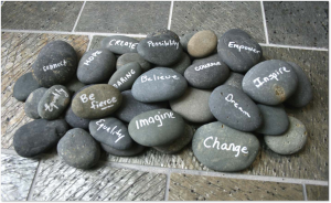 gray stones with uplifting quotes on them