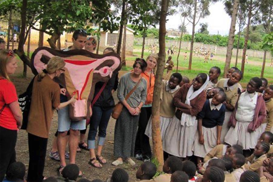UW students teach reproductive health (June 2012). Photographed with an anatomical felt design of the uterus in front of school children.