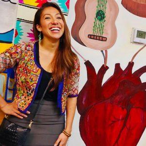 Erika Rosales smiling infront of art work